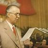 Enver Hoxha í ræðustól með fána albanska kommúnistaflokksins í baksýn.