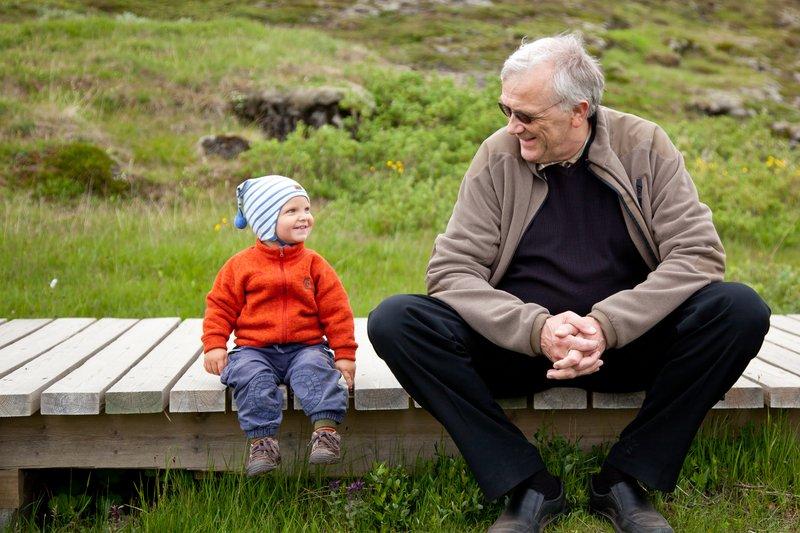 Þórarinn situr hér og rabbar við barnabarn sitt, Ólíver Daða, á Þingvöllum.