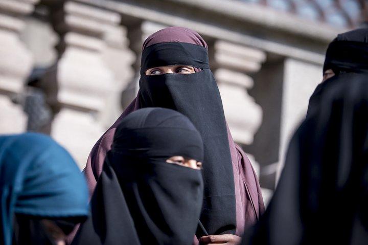Nokkrar konur íklæddar niqab yfirgefa danska þingið eftir að lögin voru samþykkt.