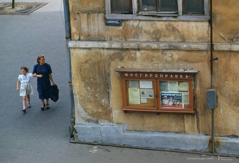 Kona og barn ganga á horni Bolshoi Devyatinsky pereulok og Novinsky bulvar nærri bandaríska sendiráðinu í Moskvu.